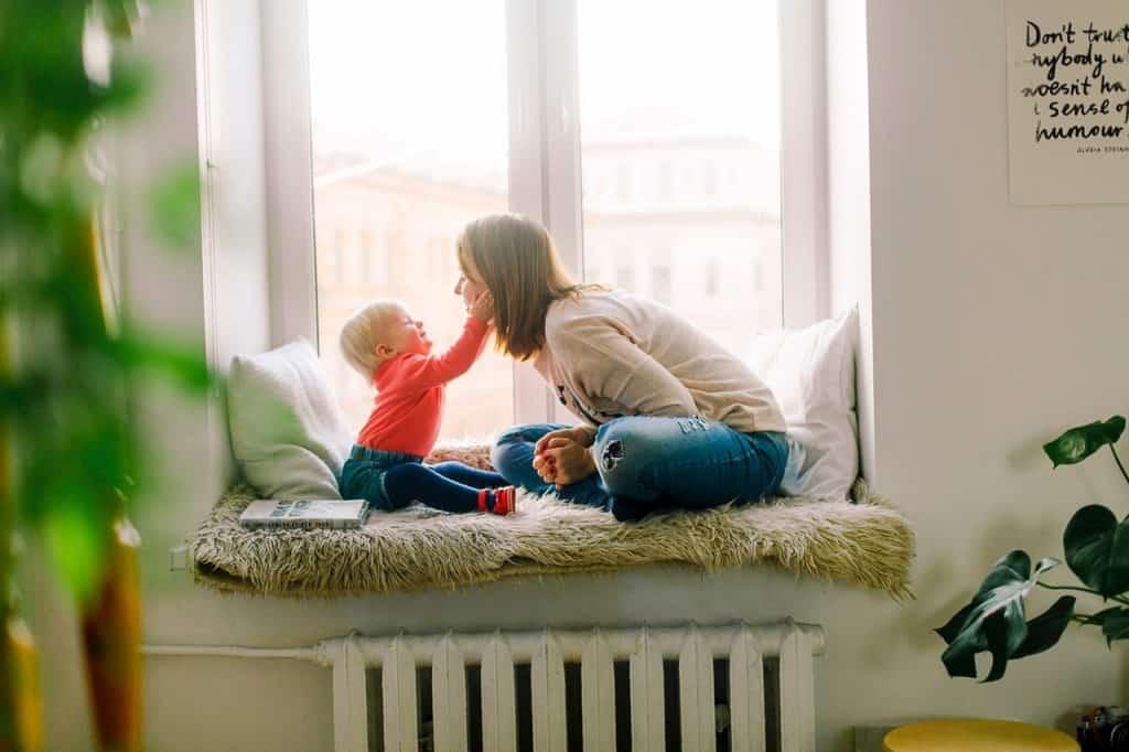 Na foto uma mulher com uma bebê sentadas em frente a uma janela.