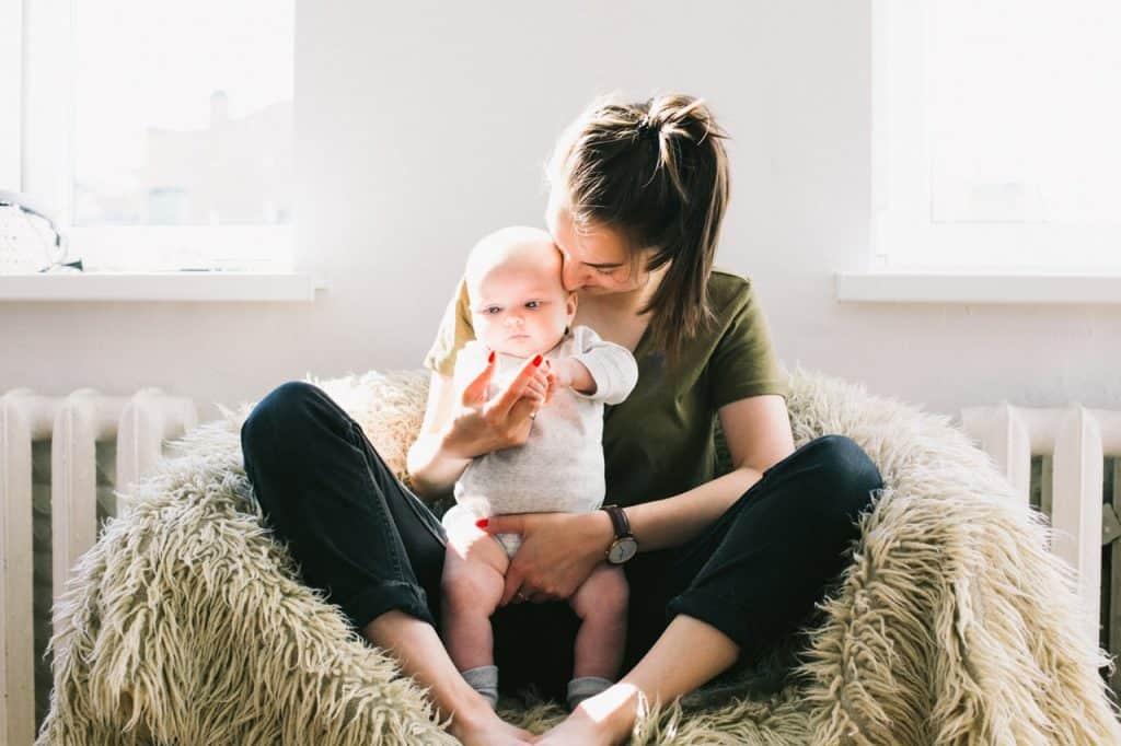 Na foto estão uma mulher e um bebê sentados em uma poltrona de pelos.