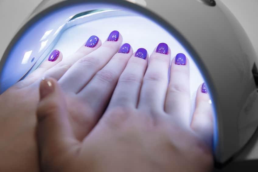 Foto de duas mãos dentro de uma câmara de LED.