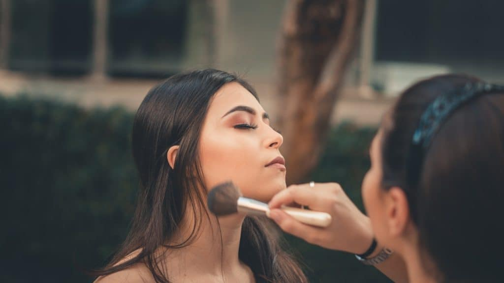 Foto de uma mulher sendo maquiada por uma outra pessoa. Na imagem, a maquiadora passa blush na bochecha da modelo.