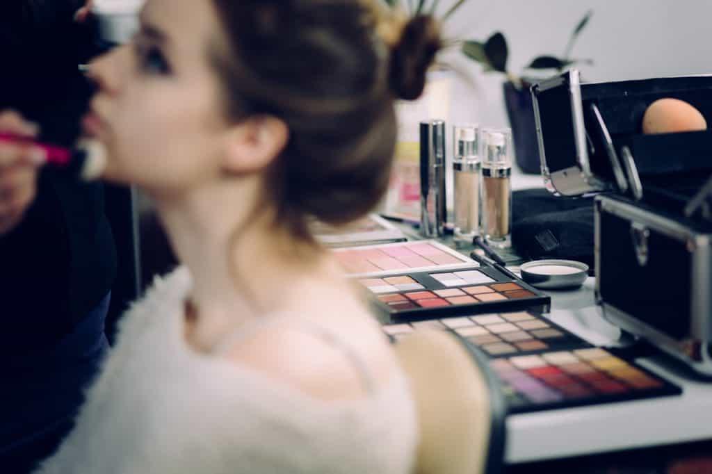 Foto de uma mulher em primeiro plano, mas em blur, sentada em uma cadeira sendo maquiada. Ao funcho, sem blur, uma mesa com diversas maquiagens, incluindo várias paletas de sombras.