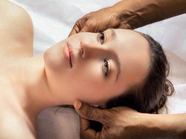 A imagem mostra o rosto de uma mulher deitada, com o rosto em close e duas mãos de outra pessoa fazendo massagem nas bochechas dela, próximo às orelhas.