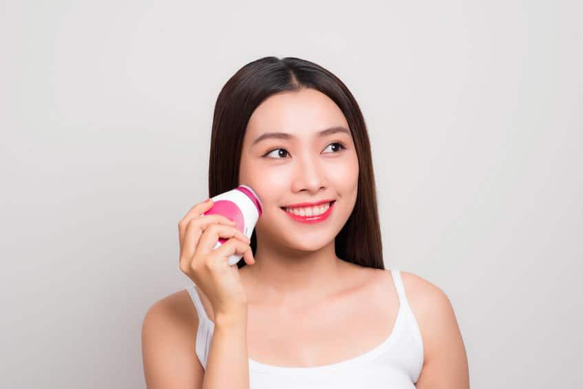 A imagem mostra uma mulher sorrindo e segurando um massageador facial.