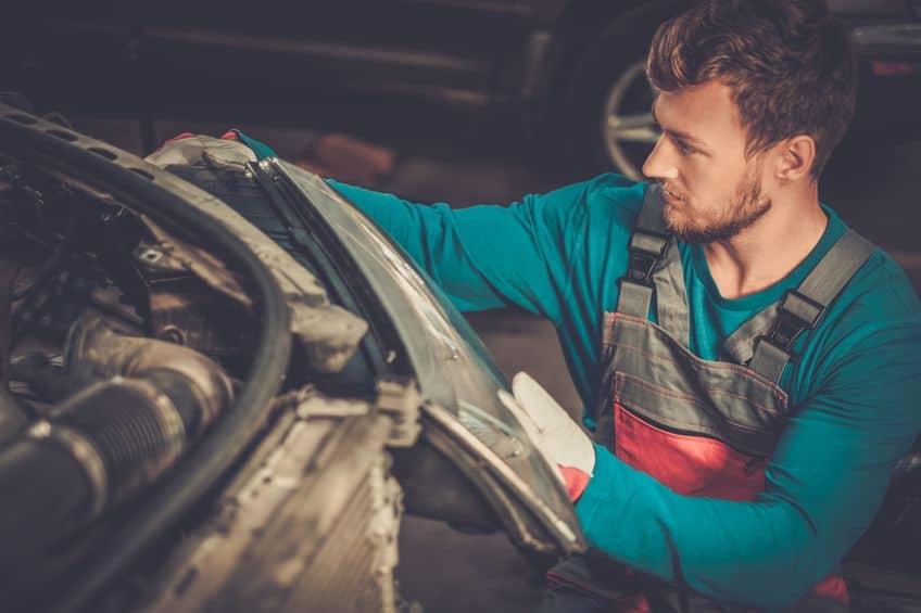 Mecânico mexendo em farol de carro.