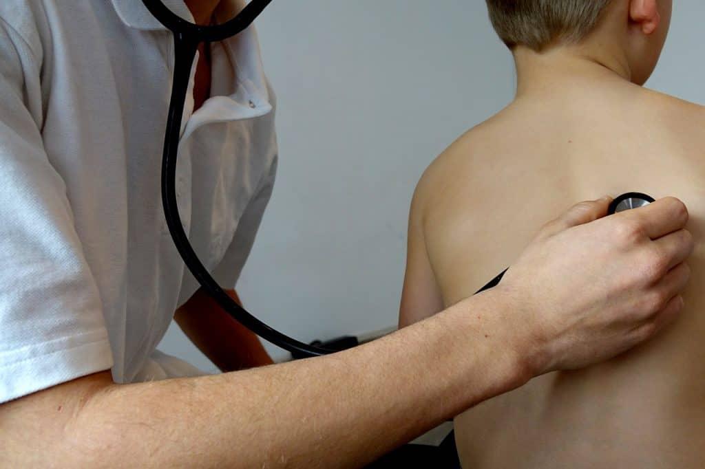 Imagem de um médico examinando uma criança com um estetoscópio.