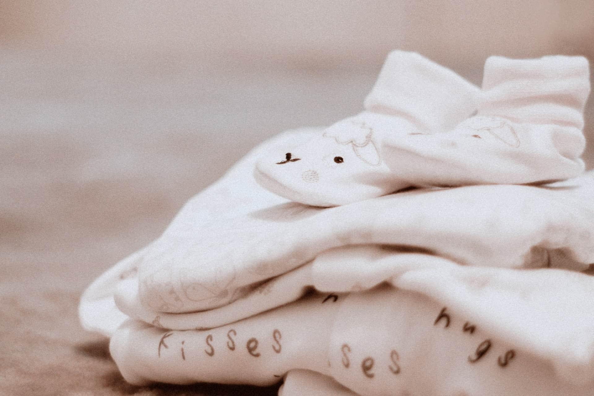 Na foto uma pilha de roupas brancas de bebê com um par de meias em cima com estampa de ovelha.