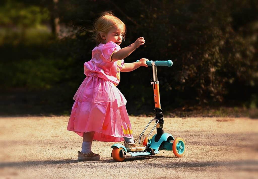Imagem destaca uma menininha de vestido rosa com um dos pés sobre um patinete.