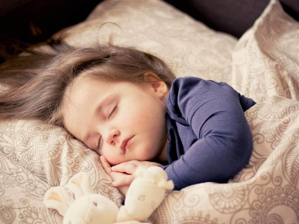 Menina dorme coberta com edredom.
