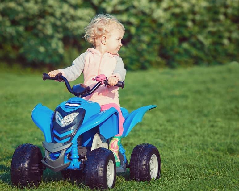 Criança pilotando um quadriciclo infantil azul sobre a grama.