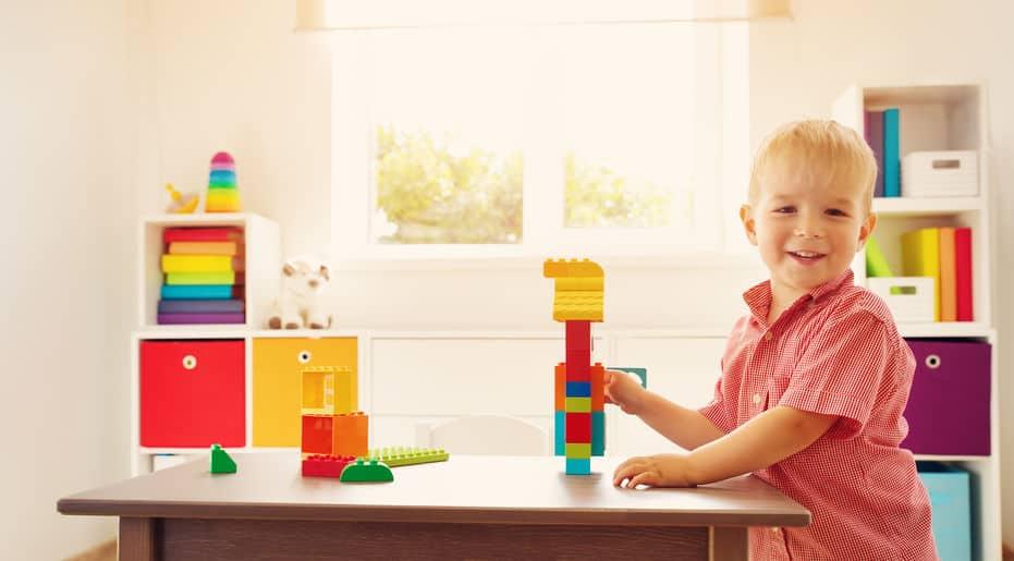 Garoto brincando com blocos em uma mesa, no fundo há estantes organizadores de brinquedos.