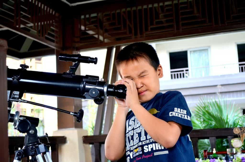 Menino brincando com telescópio.