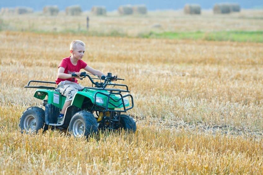 Criança pilotando um quadriciclo infantil verde em campo.