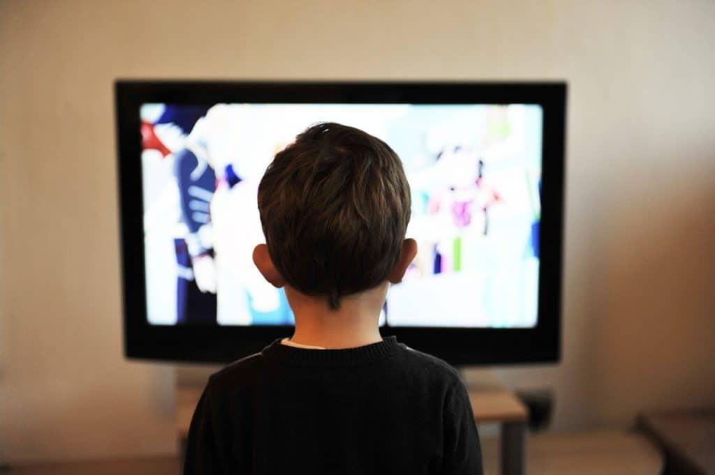 Criança de frente para a televisão presa na parede.