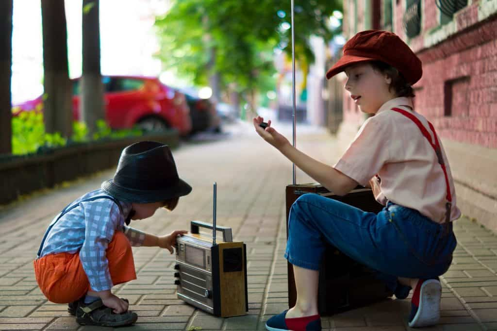 Two children are on a sidewalk.  The smallest is crouched in front of a small portable radio.  The other, bigger, is crouched with a bigger portable radio.  Both wear clothes that go back to ancient times.