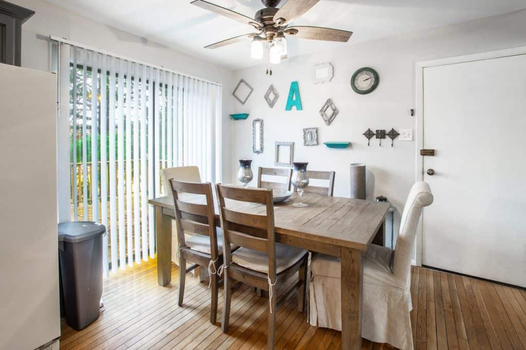 Foto de uma sala de jantar com mesa de madeira, seis cadeiras, parede branca com algumas molduras penduradas, ventilador de teto, janela com persiana, e porta branca. Em cima da mesa, três diferentes centros de mesa.