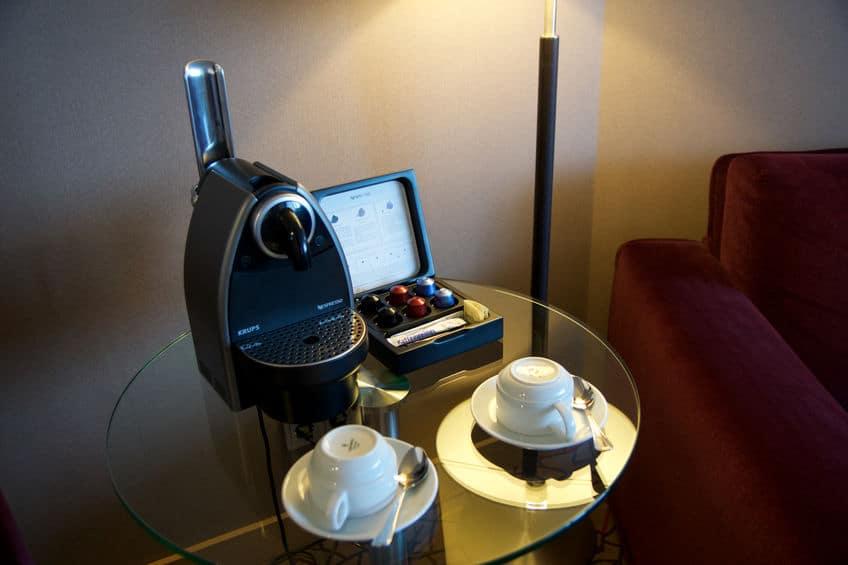 Imagem de mesa com cafeteira, cápsulas de café e xícaras.