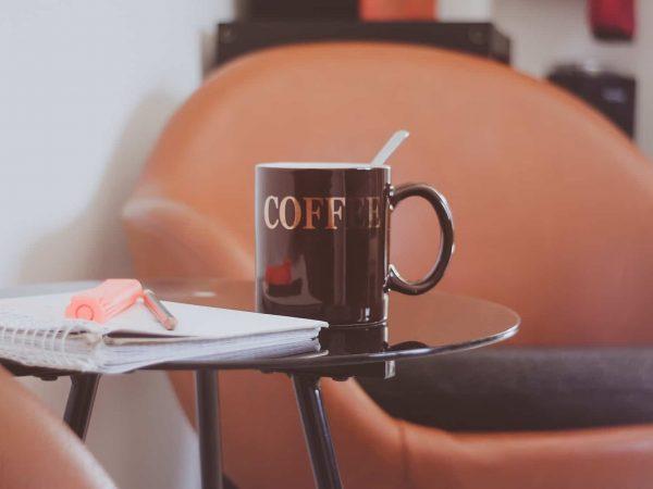 A imagem mostra, em foco, uma mesa de canto preta com uma xícara de café, um caderno e duas canetas em cima. Ao fundo, desfocado, há uma cadeira marrom.