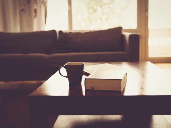 Imagem de mesa de centro de sala com livro e xícara em cima.