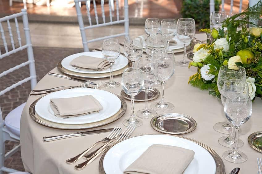 Imagem de mesa de jantar de madeira com sousplat marrons sob pratos brancos.
