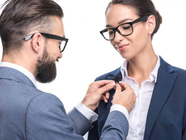 Na foto um homem colocando um microfone de lapela em uma mulher.
