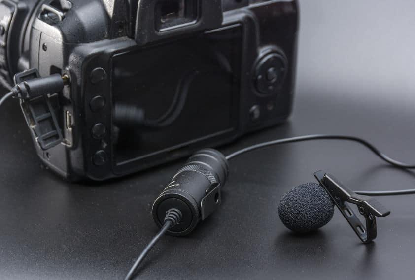 Na foto um microfone de lapela conectado a uma câmera digital.