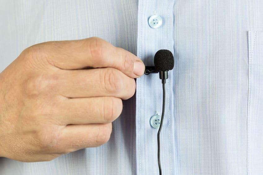 Na foto a mão de um homem segurando um microfone de lapela em frente e uma camisa azul.
