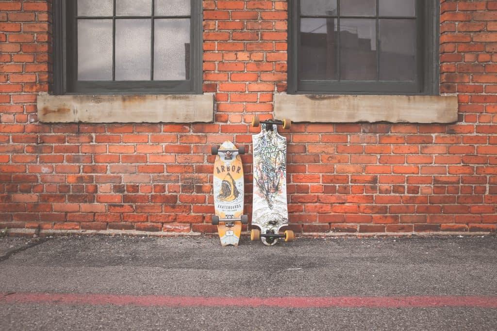 Imagem mostra dois modelos de longboard diferentes lado a lado, ambos encostados sob uma parede de tijolos à vista.