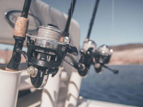 Imagem mostra molinetes em varas de pesca colocadas em um barco.