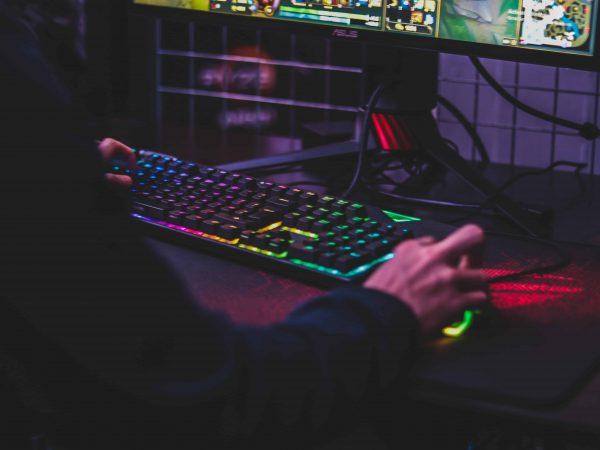 Imagem mostra um teclado gamer e pessoa com a mão em cima de mouse gamer em um mouse pad gamer.