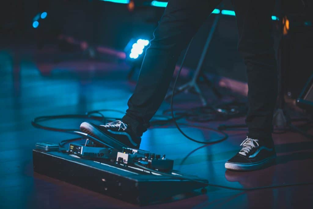 Photo of a presentation, where the guitarist's feet are being stepped on one of the pedalboards, to activate it.