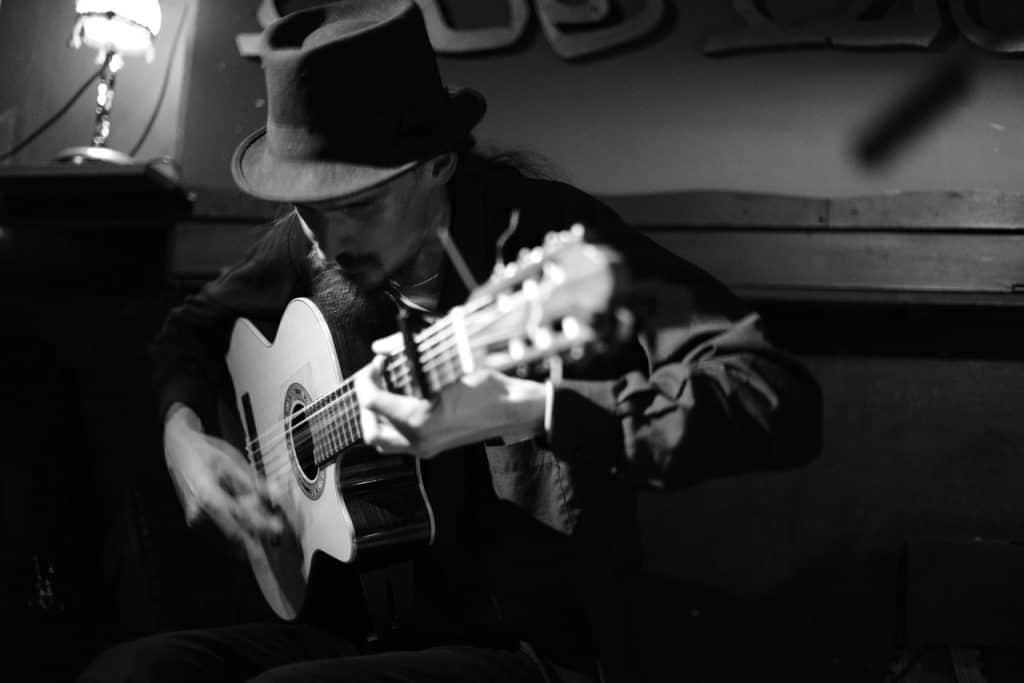 Um músico com chapéu negro e camiseta longa preta. Ele toca violão com capotraste em uma sala iluminada apenas por um abajur.