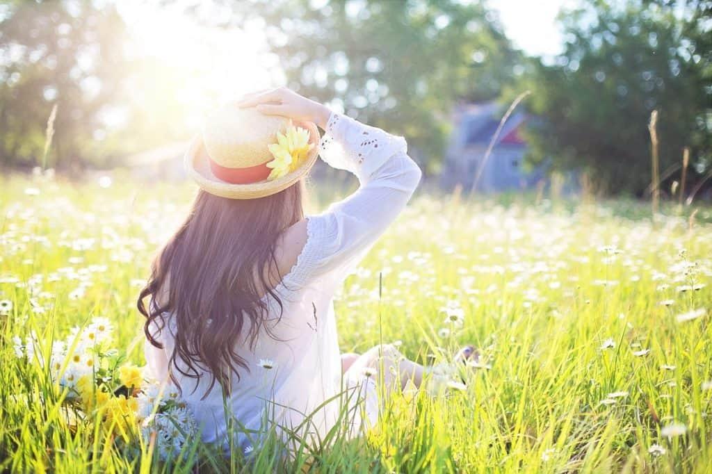 Imagem de mulher sentada de costas na natureza com cabelos brilhosos.