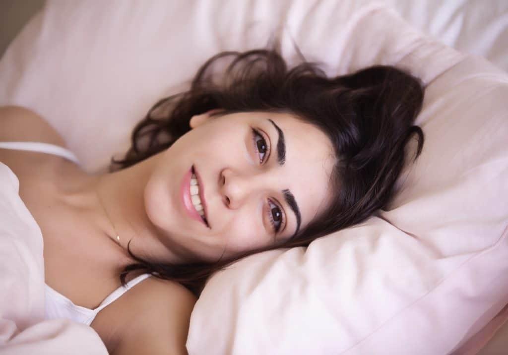 Foto de uma mulher de cabelo preto e rosto lavado, deitada em um travesseiro, levemente coberta, sorrindo para a câmera.