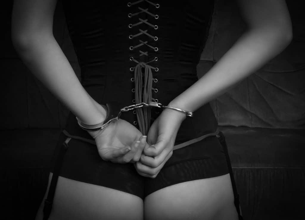 Imagem de mulher algemada usando espartilho preto.