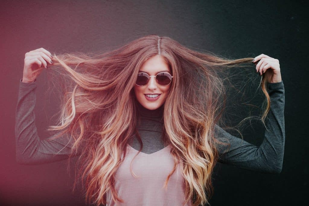 Imagem de mulher loira sorrindo segurando o cabelo.
