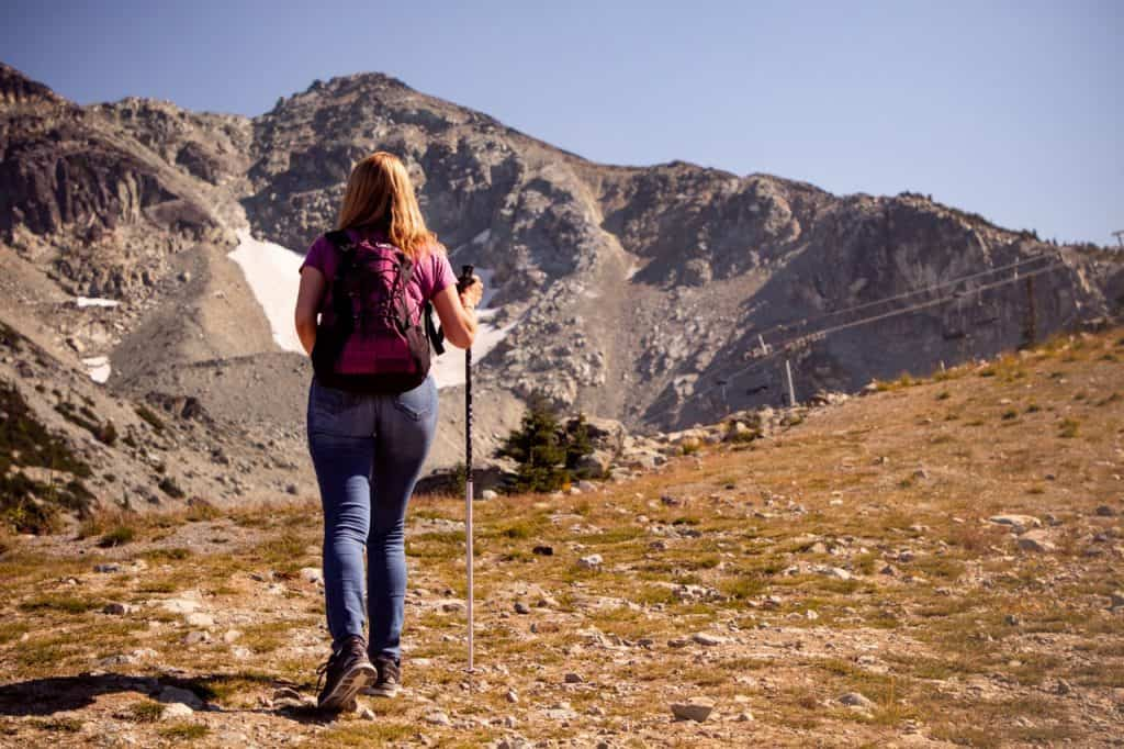 Imagem mostra uma moça, de costas para a câmera, fazendo uma caminhada, usando um bastão em sua mão direita. Ao fundo, uma paisagem montanhosa.