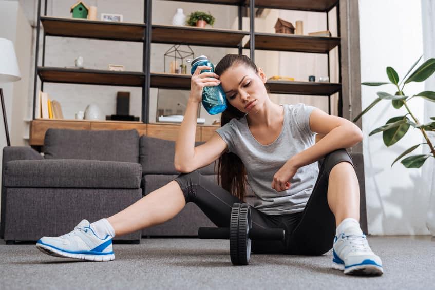 Imagem de mulher descansando após realizar uma rotina em sua roda de exercícios.