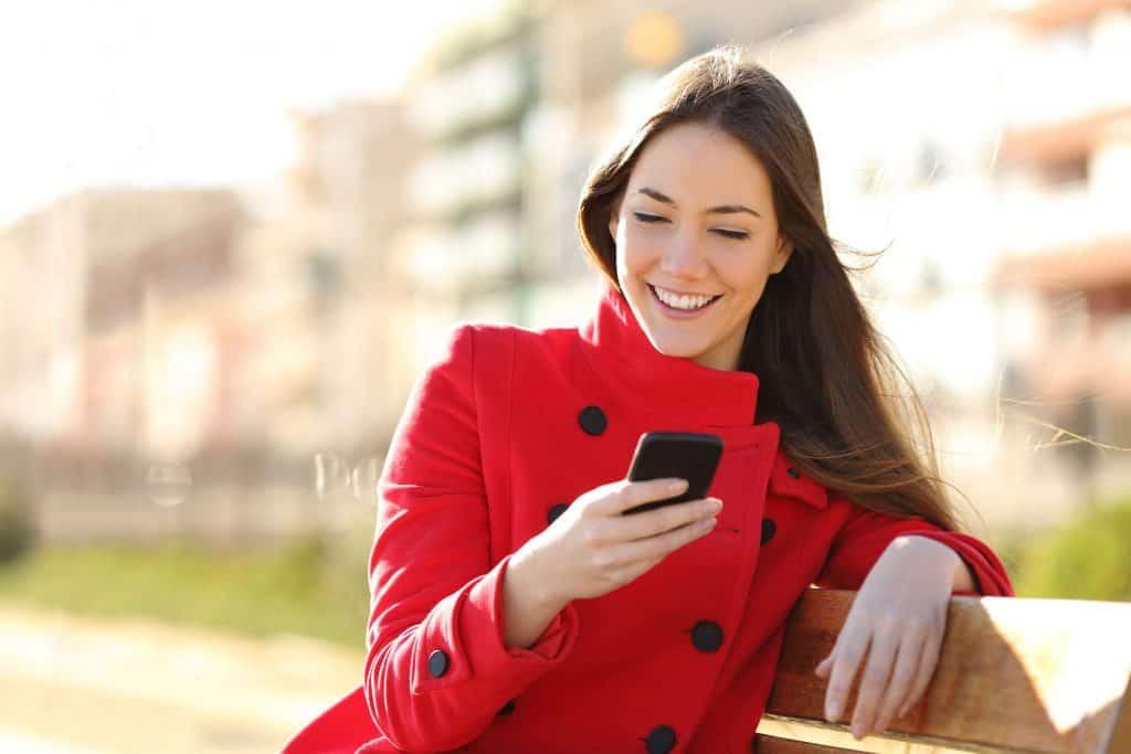 Garota sentada em banco ao ar livre sorrindo e mexendo em um smartphone.
