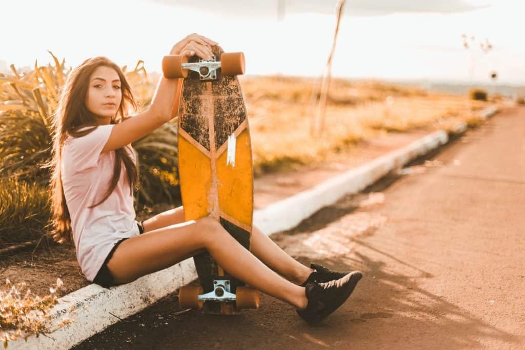 """Imagem mostra uma moça sentada no meio fio de uma rua, com longboard entre as pernas. Seu joelho se apoia em duas rodas e suas mãos no """"bico"""" do shape."""