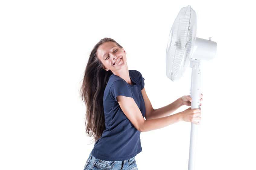 Imagem de mulher segurando ventilador coluna.