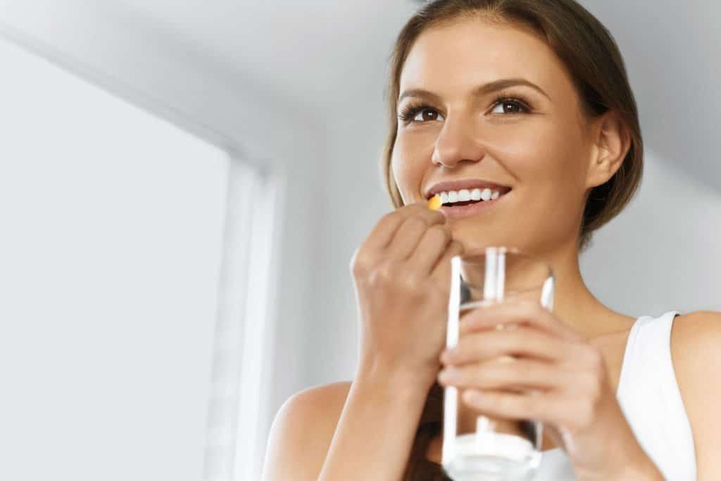 mulher jovem sorrindo e ingerindo cápsula, ela está segurando a cápsula em uma mão e o copo de água na outra