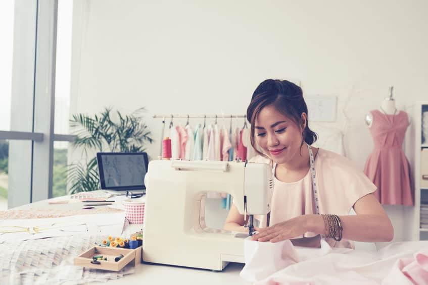 Mulher costurando em máquina de costura portátil em um ateliê.