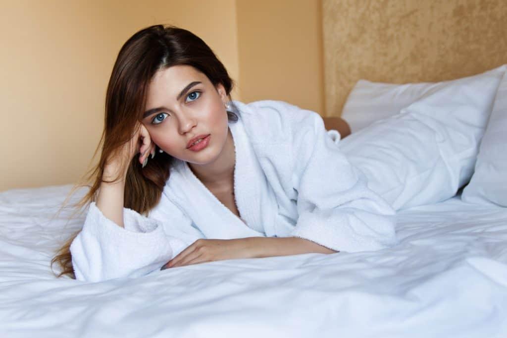 imagem de uma moça deitada em uma cama.