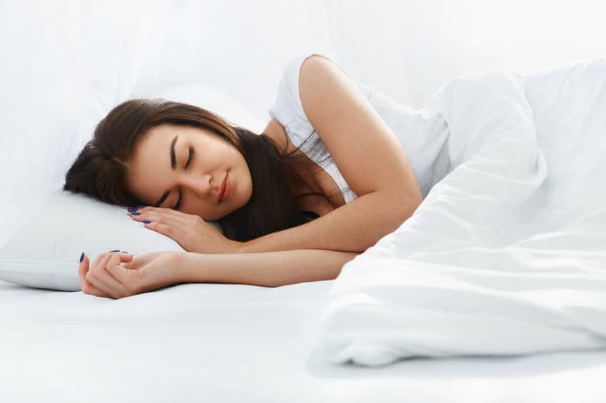 Mulher dormindo em uma cama com as roupas de cama todas brancas.