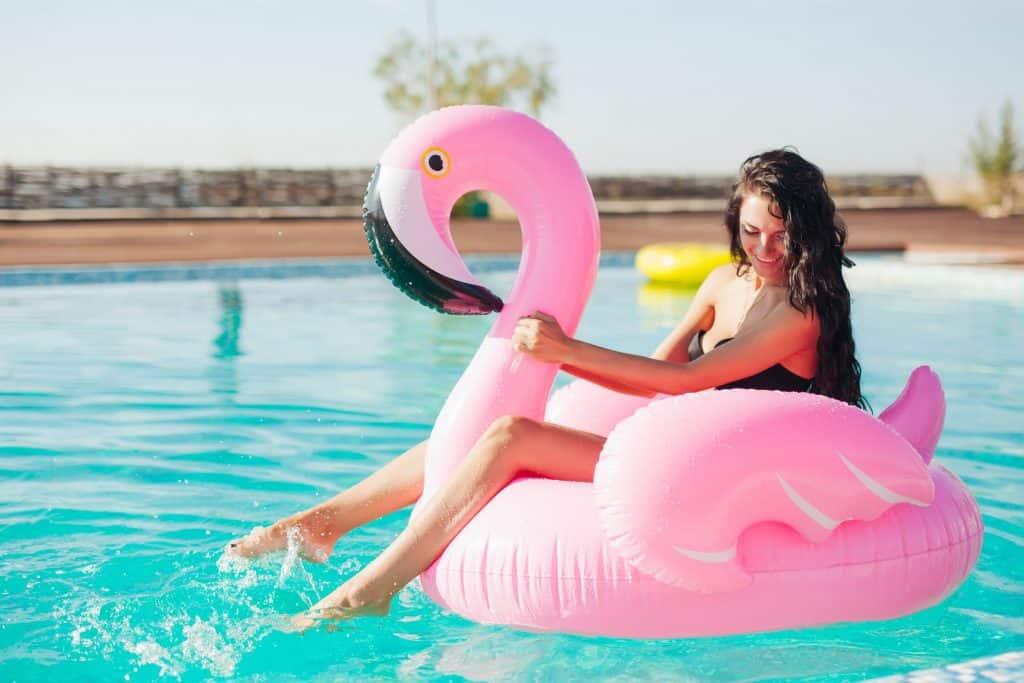 pernas de uma mulher sentada em uma boia de flamingo na piscina.