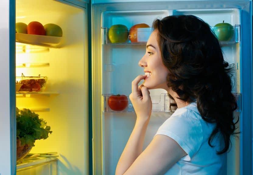 Mulher em frente a geladeira escolhendo o que comer.