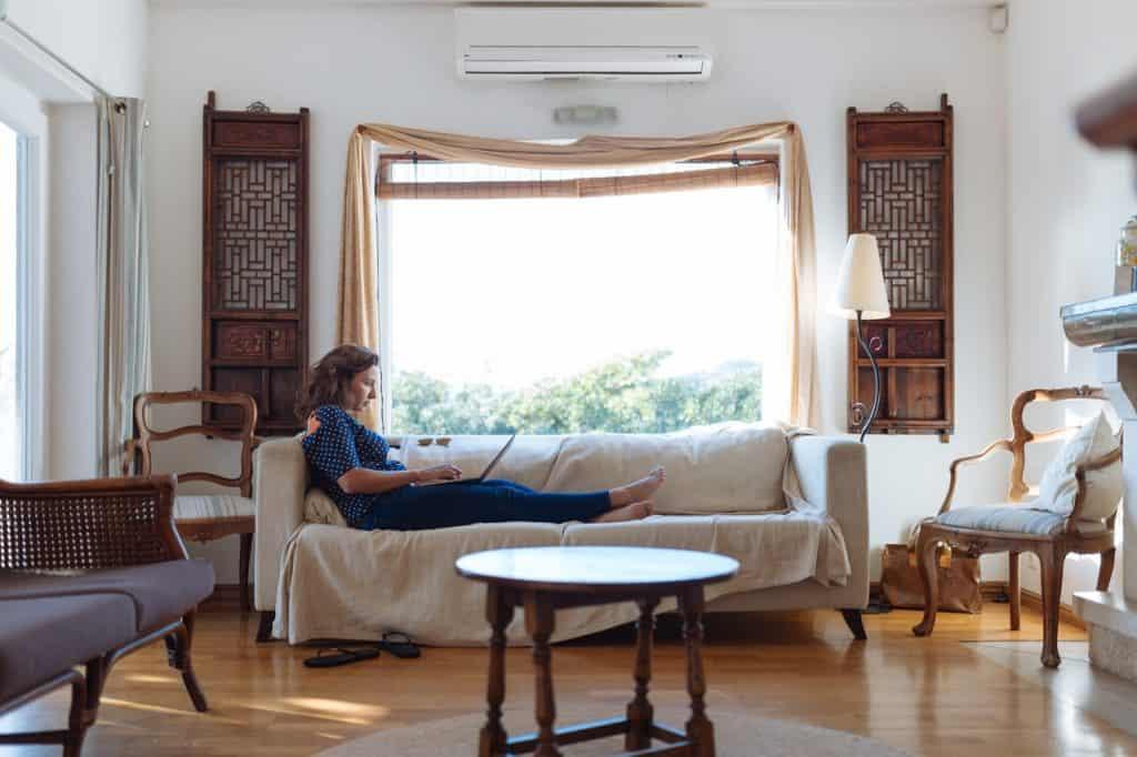 Imagem de mulher trabalhando em notebook em um sofá com capa protetora branca.