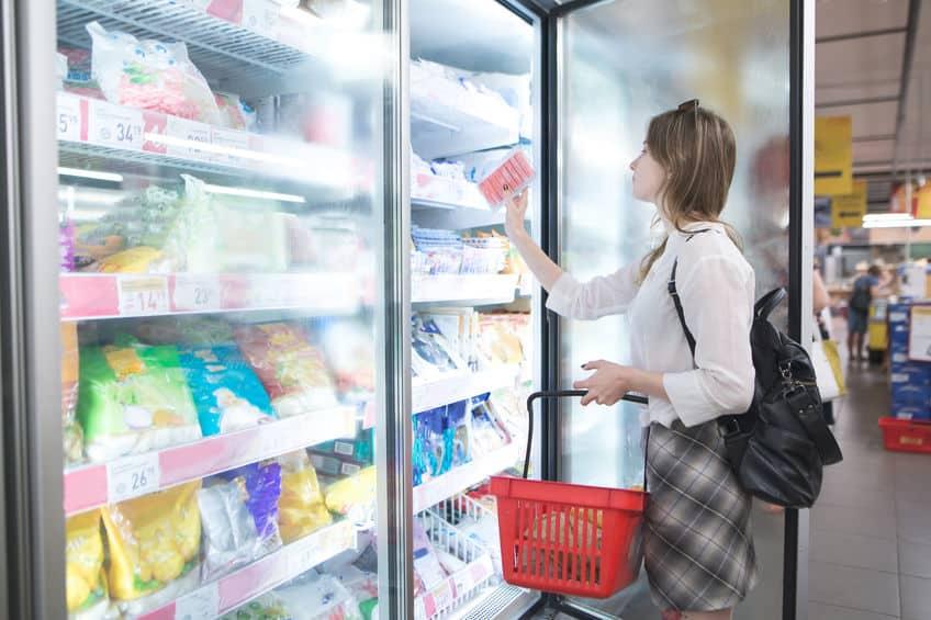 Mulher segurando uma cestinha e abrindo porta de freezer vertical e pegando alimentos de dentro.