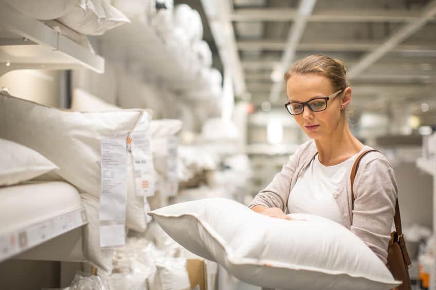 Imagem mostra mulher comprando travesseiro em uma loja.