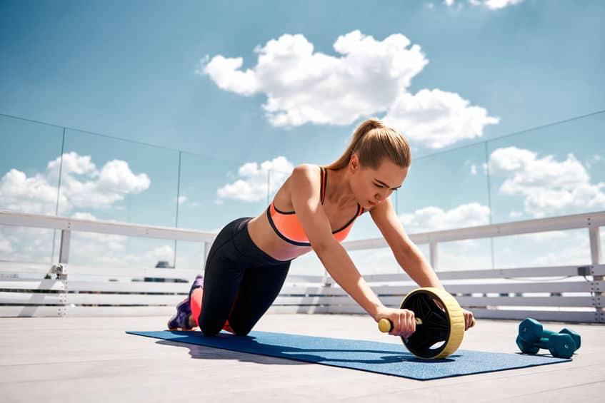 Imagem de mulher utilizando roda de exercícios abdominais ao ar livre.